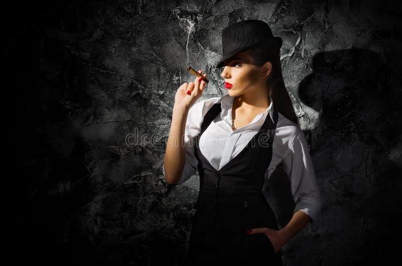 Επικίνδυνο και όμορφο εγκληματικό κορίτσι με το πούρο στοκ φωτογραφία