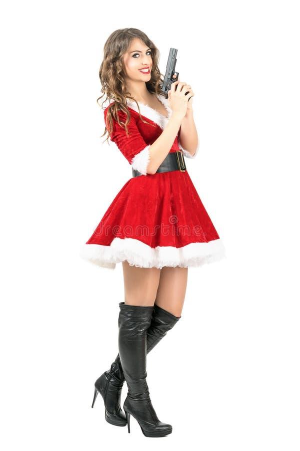 Επικίνδυνο κακό πυροβόλο όπλο εκμετάλλευσης γυναικών Santa με το κακό χαμόγελο που εξετάζει τη κάμερα στοκ φωτογραφία με δικαίωμα ελεύθερης χρήσης