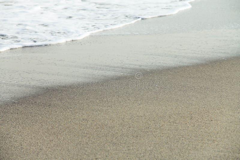 Επικείμενος αφρός κυμάτων στην παραλία στοκ φωτογραφία