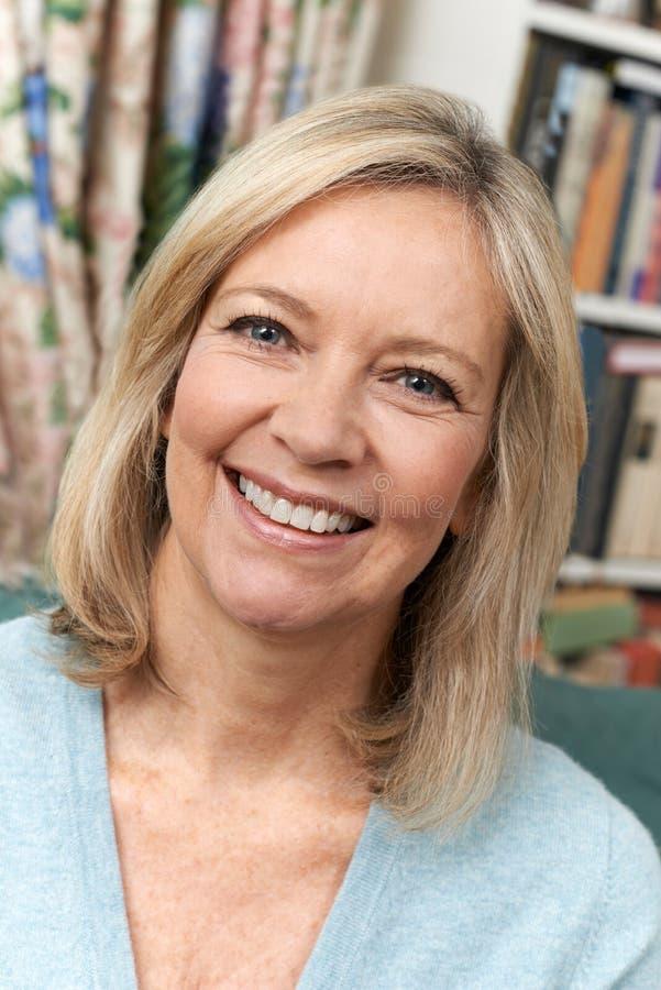 Επικεφαλής και πορτρέτο ώμων της χαμογελώντας ώριμης γυναίκας στο σπίτι στοκ φωτογραφία