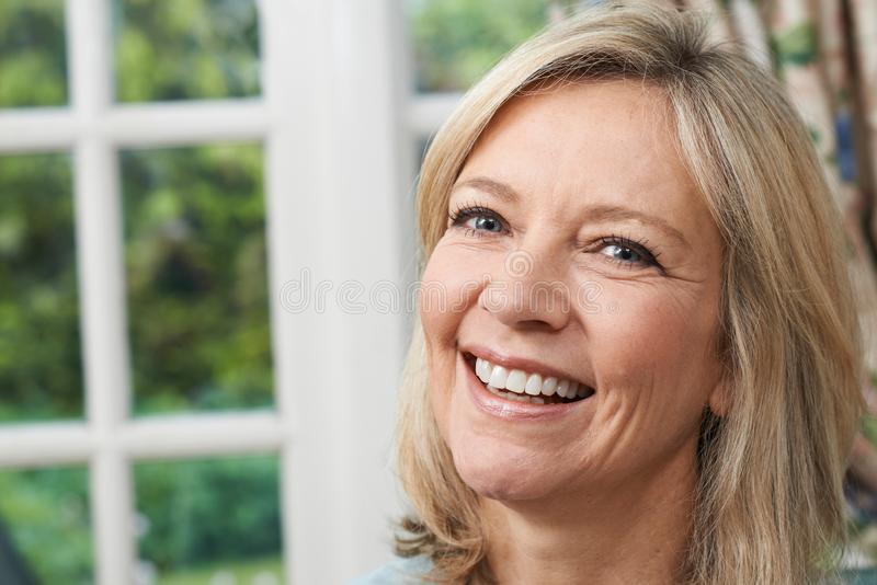 Επικεφαλής και πορτρέτο ώμων της χαμογελώντας ώριμης γυναίκας στο σπίτι στοκ φωτογραφίες