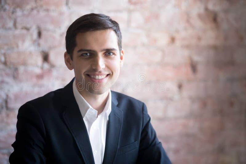 Επικεφαλής πυροβολισμός του πορτρέτου του χαμογελώντας και ευτυχούς επιτυχούς αρσενικού επιχειρηματία στοκ φωτογραφία