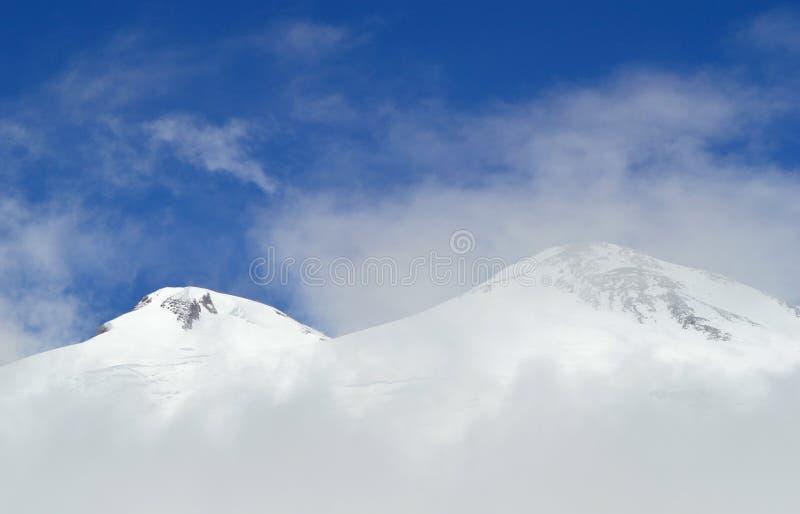 Επικεφαλής του βουνού Elbrus που αντιμετωπίζεται μέσω της ομίχλης και των σύννεφων στοκ φωτογραφία με δικαίωμα ελεύθερης χρήσης