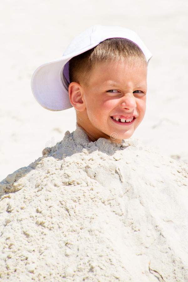Επικεφαλής ενός αγοριού στην ΚΑΠ που θάβεται στην άμμο στοκ εικόνα