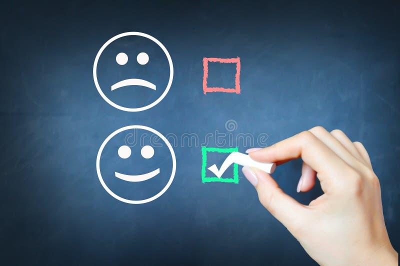 Επιλέξτε να είστε ευχαριστημένος από τον κρότωνα ενάντια στο πρόσωπο smiley στον πίνακα κιμωλίας στοκ εικόνα με δικαίωμα ελεύθερης χρήσης