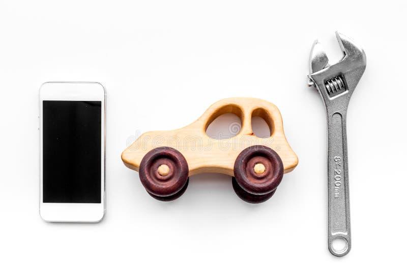 Επιλέξτε την υπηρεσία αυτοκινήτων Γαλλικό κλειδί κοντά στα παιχνίδια αυτοκινήτων και τηλέφωνο κυττάρων στην άσπρη τοπ άποψη υποβά στοκ φωτογραφία