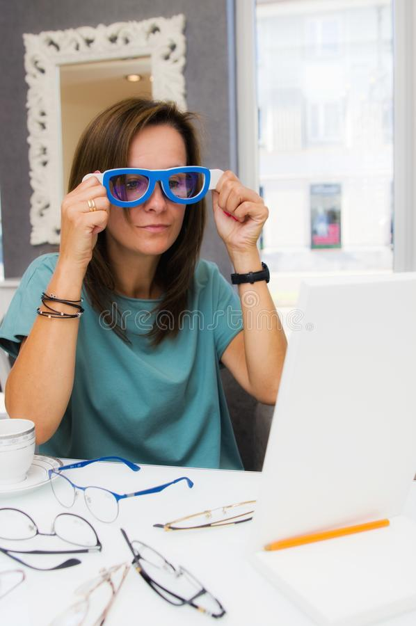 Επιλογή γυναικών Brunette και eyeglasses αγοράς στο σαλόνι ή το κατάστημα οπτικών στοκ φωτογραφίες με δικαίωμα ελεύθερης χρήσης