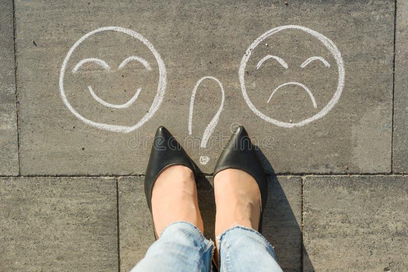 Επιλογή - ευτυχές Smileys ή δυστυχισμένος, κείμενο στο δρόμο ασφάλτου στοκ φωτογραφίες
