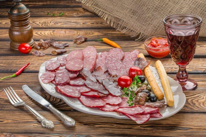 Επιλογή ορεκτικών κρέατος Σαλάμι, prosciutto, ραβδιά ψωμιού, ελιές και ξηραμένες από τον ήλιο ντομάτες, ένα κόκκινο κρασί glasse  στοκ φωτογραφία