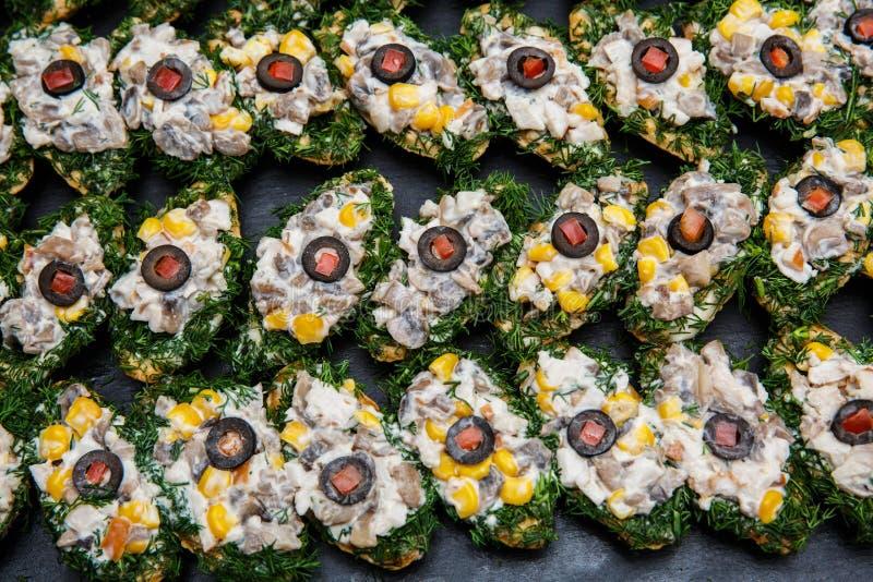 Επιλογή του νόστιμων bruschetta ή των καναπεδάκια στο ψημένο baguette με τα μανιτάρια, καλαμπόκι, μάραθο, ελιά, ντομάτα, μαγιονέζ στοκ φωτογραφία
