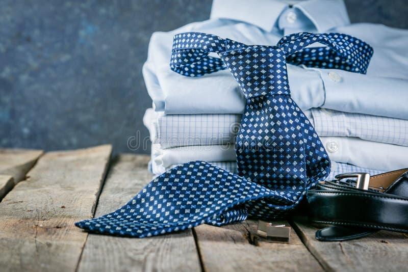 Επιλογή των αρσενικών ενδυμάτων - σωρός των διπλωμένων πουκάμισων, δεσμός, ζώνη, μανικετόκουμπα στοκ εικόνες