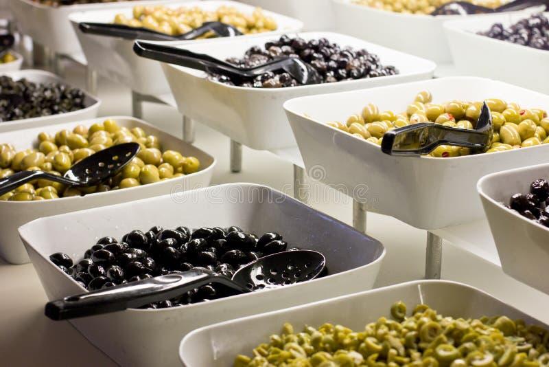 Επιλογή των μαύρων και πράσινων ελιών στα άσπρα κύπελλα στοκ φωτογραφίες