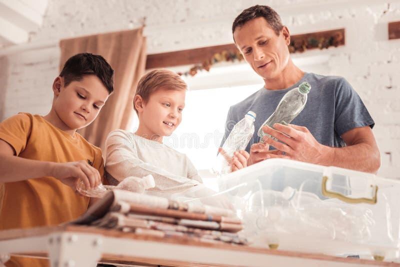 Επιμελής πατέρας που μιλά με τους γιους του για την ταξινόμηση αποβλήτων στοκ φωτογραφίες με δικαίωμα ελεύθερης χρήσης