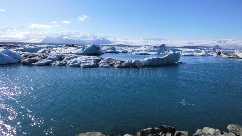 Επιπλέοντα μπλε παγόβουνα στην μπλε λίμνη και την άποψη βουνών στοκ φωτογραφίες