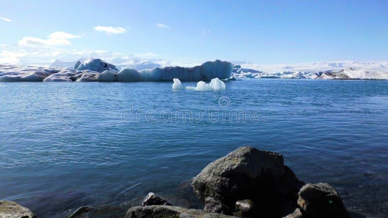 Επιπλέοντα μπλε παγόβουνα στην μπλε λιμνοθάλασσα και την άποψη βουνών στοκ εικόνες με δικαίωμα ελεύθερης χρήσης