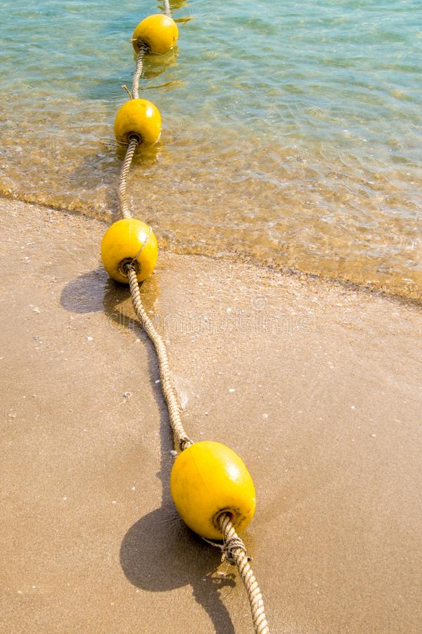Επιπλέοντες σημαντήρας και σχοινί που διαιρούν την περιοχή στην παραλία στοκ εικόνα