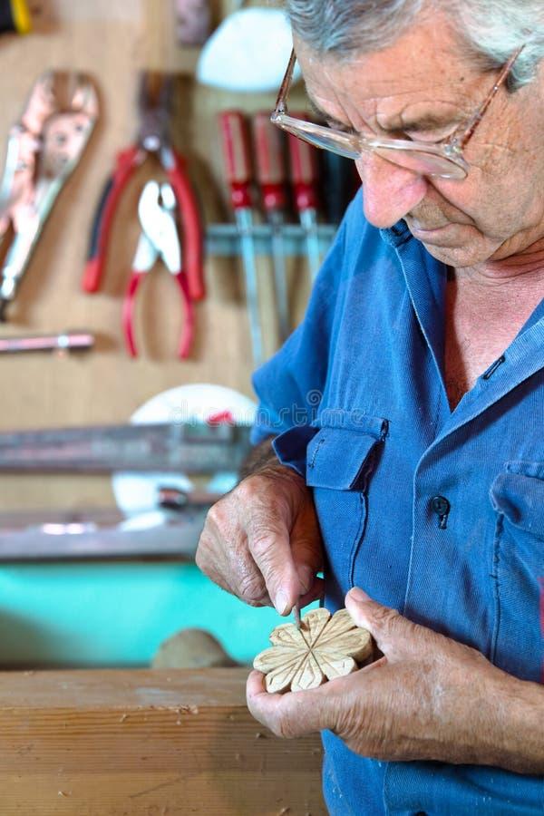Επιπλοποιός που στρώνει με άμμο ένα διακοσμητικό κομμάτι του ξύλου στοκ φωτογραφίες με δικαίωμα ελεύθερης χρήσης