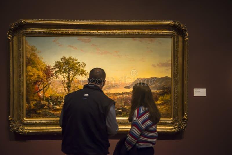Επισκέπτες κοιτάζουν τον Jasper Francis Cropsey ζωγραφίζοντας το Ινδικό Καλοκαίρι του 1866 στοκ φωτογραφία με δικαίωμα ελεύθερης χρήσης