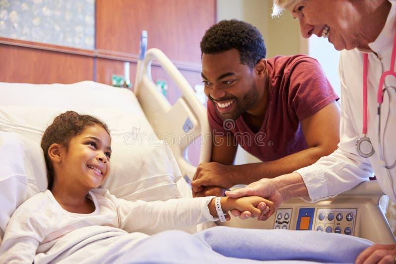 Επισκεπτόμενοι πατέρας και παιδί παιδιάτρων στο νοσοκομειακό κρεβάτι στοκ φωτογραφίες