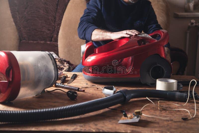 Επισκευές ατόμων της ηλεκτρικής σκούπας Επισκευή στοκ εικόνες