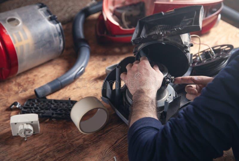 Επισκευές ατόμων της ηλεκτρικής σκούπας Επισκευή στοκ φωτογραφία με δικαίωμα ελεύθερης χρήσης