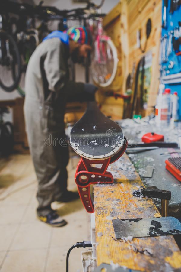 Επισκευές θέματος και συντήρηση των σκι Ο άνδρας εργαζόμενος επισκευάζει τα ενδύματα εργασίας, εφαρμόζοντας το κερί στην επιφάνει στοκ εικόνα με δικαίωμα ελεύθερης χρήσης