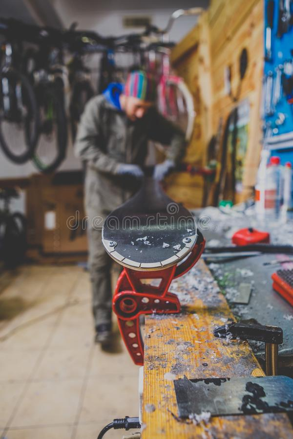 Επισκευές θέματος και συντήρηση των σκι Ο άνδρας εργαζόμενος επισκευάζει τα ενδύματα εργασίας, εφαρμόζοντας το κερί στην επιφάνει στοκ φωτογραφία με δικαίωμα ελεύθερης χρήσης