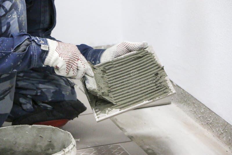 επισκευές Τοποθέτηση των κεραμικών κεραμιδιών πατωμάτων Τα άτομα ` s παραδίδουν τα γάντια με spatula, κονίαμα τσιμέντου στο κεραμ στοκ φωτογραφία με δικαίωμα ελεύθερης χρήσης