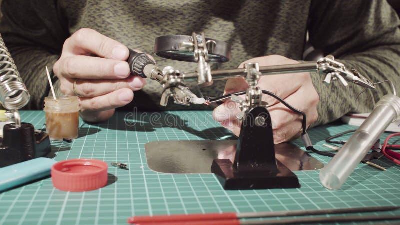 Επισκευή ενός καλωδίου για τις ηλεκτρονικές συσκευές Αρσενικά χέρια που συγκολλούν το καλώδιο στοκ φωτογραφία με δικαίωμα ελεύθερης χρήσης