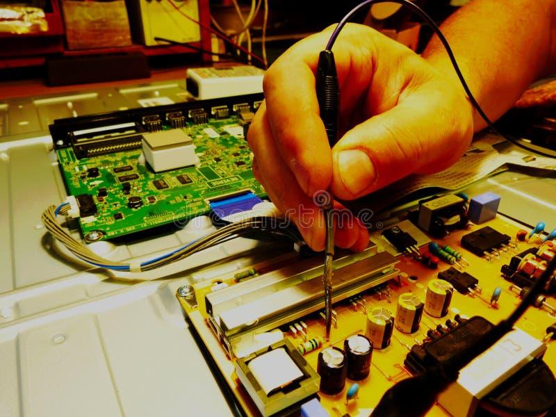 Επισκευή ηλεκτρονικής TV με την αφαιρούμενη πίσω επιτροπή και τις εκτεθειμένες επιτροπές πινάκων Αρσενικός μετρητής βολτ εκμετάλλ στοκ φωτογραφία με δικαίωμα ελεύθερης χρήσης