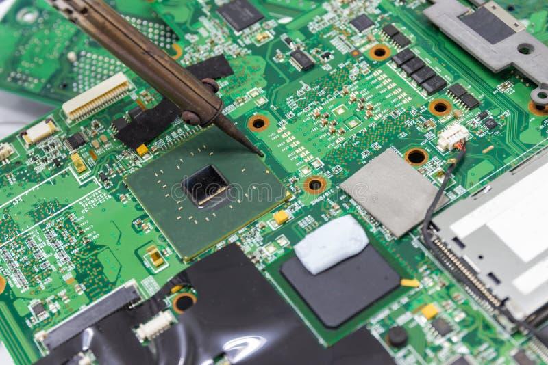 Επισκευή τεχνικών ηλεκτρονική του πίνακα κυκλωμάτων υπολογιστών ` s από τους συγκολλώντας σιδήρους στοκ εικόνες