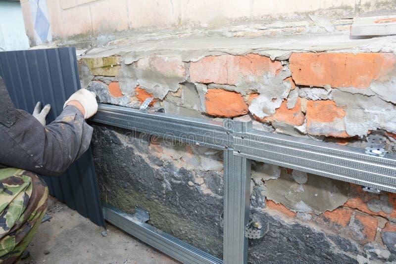 Επισκευή τοίχου από το κτίριο του Brick House, ανακαίνιση με χέρια οικοδόμων που εγκαθιστούν μεταλλικά φύλλα για στεγανοποίηση κα στοκ εικόνα με δικαίωμα ελεύθερης χρήσης