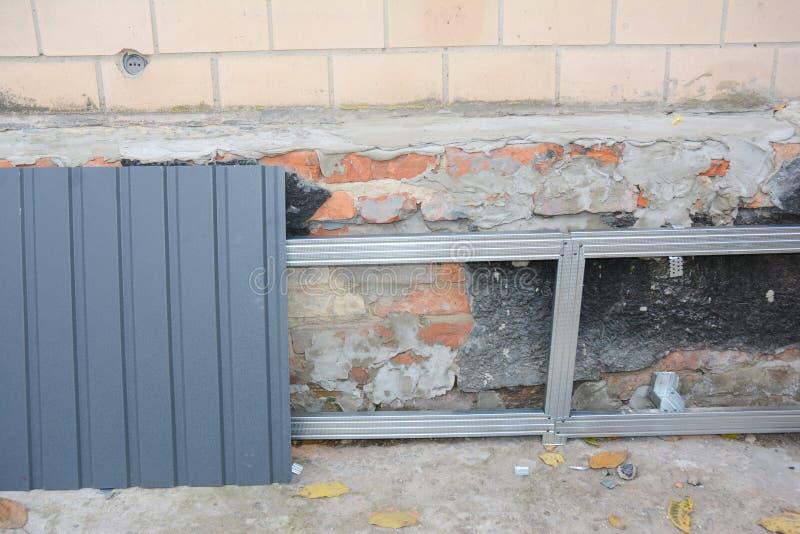 Επισκευή τοίχου του κτιρίου του σπιτιού, επισκευή με εγκατάσταση μεταλλικών φύλλων για στεγανοποίηση και προστασία στοκ φωτογραφίες