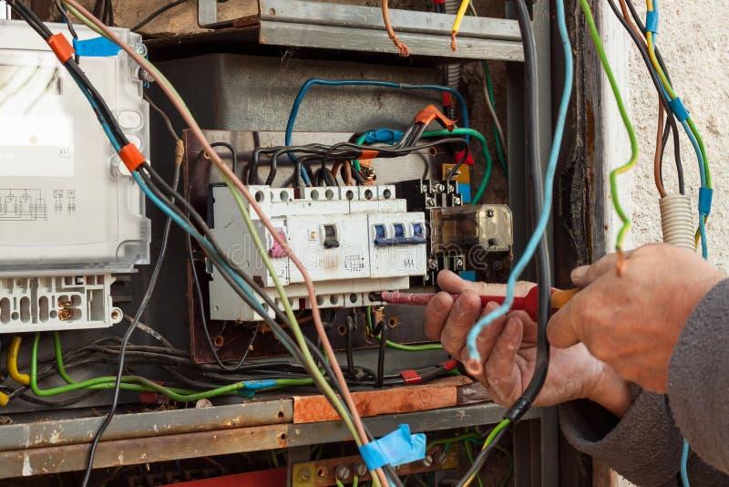 Επισκευή του παλαιού ηλεκτρικού μηχανισμού διανομής Ένας ηλεκτρολόγος αντικαθιστά τις παλαιές ηλεκτρικές συσκευές καλωδίωσης στοκ εικόνες με δικαίωμα ελεύθερης χρήσης