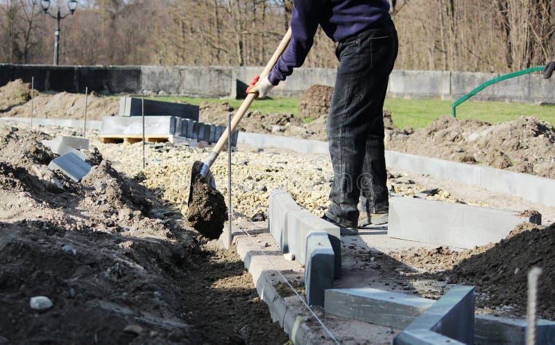 Επισκευή του πεζοδρομίου Ο εργαζόμενος λιθοδόμος επισκευάζει το πεζοδρόμιο, εγκαθιστά τις συγκρατήσεις πριν για το δρόμο πρίν βάζ στοκ εικόνα