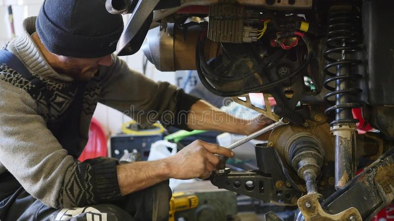 Επισκευή ATV στο γκαράζ Επισκευή ποδηλάτων τετραγώνων στοκ φωτογραφία με δικαίωμα ελεύθερης χρήσης