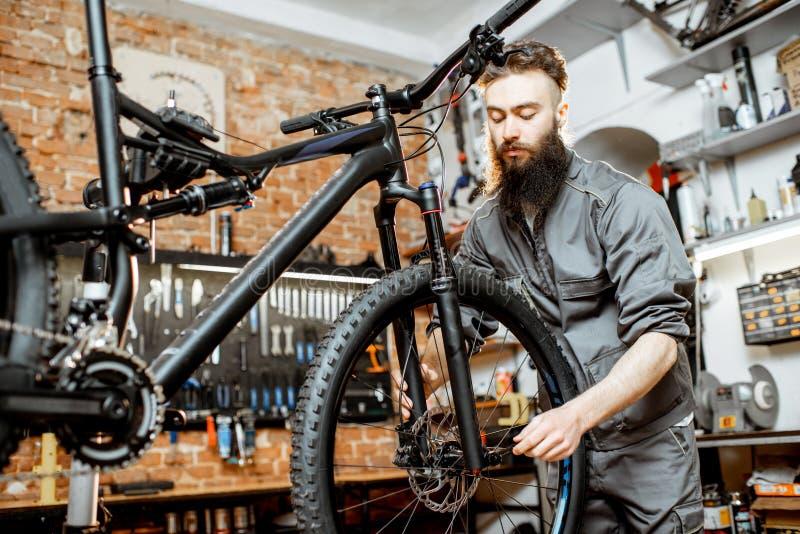 Επισκευαστής με το ποδήλατο στο εργαστήριο στοκ φωτογραφία