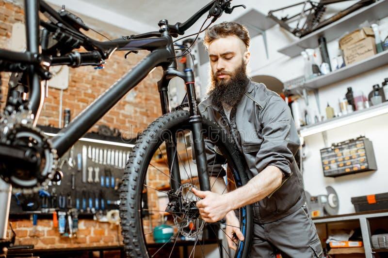 Επισκευαστής με το ποδήλατο στο εργαστήριο στοκ φωτογραφία με δικαίωμα ελεύθερης χρήσης