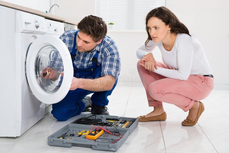 Επισκευαστής που επισκευάζει το πλυντήριο μπροστά από τη γυναίκα στοκ φωτογραφία