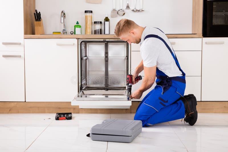 Επισκευαστής που επισκευάζει το πλυντήριο πιάτων στοκ εικόνα με δικαίωμα ελεύθερης χρήσης