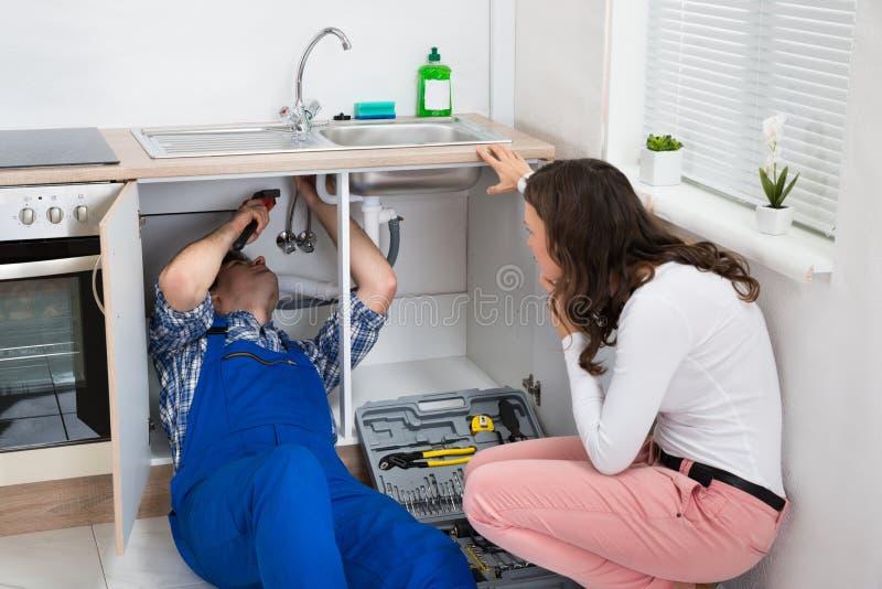 Επισκευαστής που επισκευάζει το σωλήνα ενώ γυναίκα στην κουζίνα στοκ εικόνες