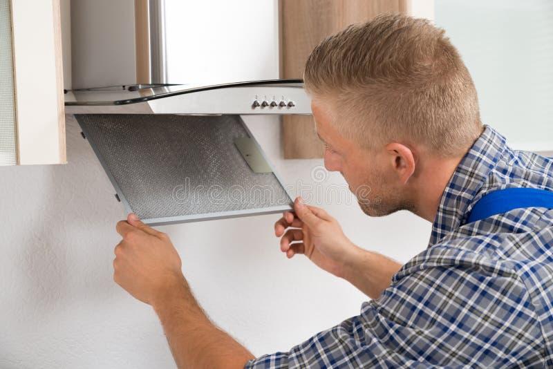 Επισκευαστής που επισκευάζει το φίλτρο εξολκέων κουζινών στοκ φωτογραφία με δικαίωμα ελεύθερης χρήσης