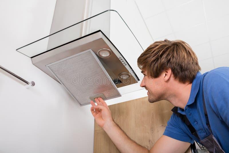 Επισκευαστής που επισκευάζει το φίλτρο εξολκέων κουζινών στοκ φωτογραφία