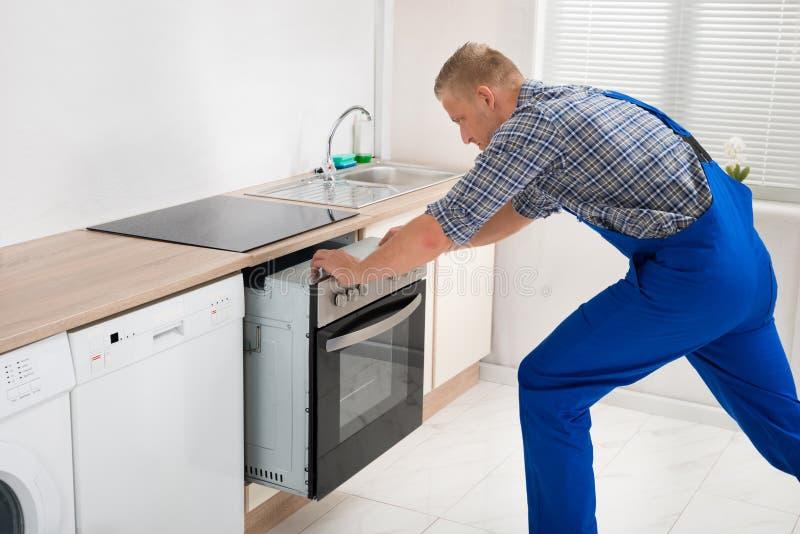 Επισκευαστής που επισκευάζει το φούρνο στοκ φωτογραφία