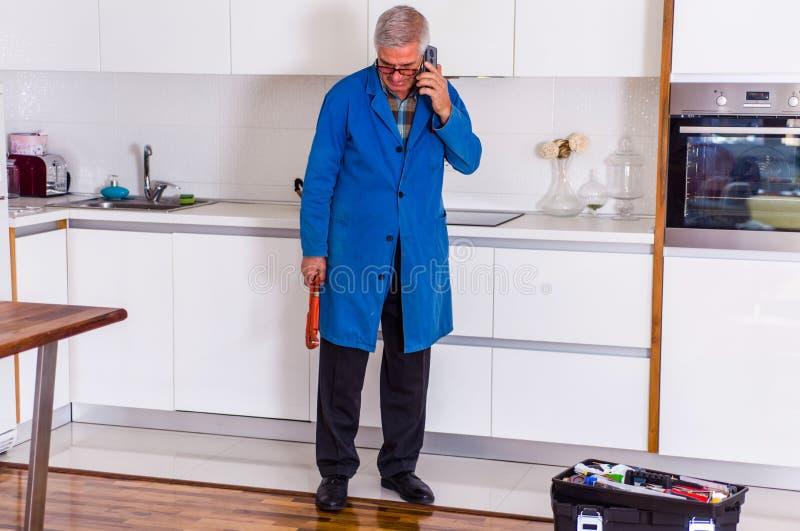 Επισκευαστής που μιλά σε κινητό στην κουζίνα στοκ εικόνα με δικαίωμα ελεύθερης χρήσης