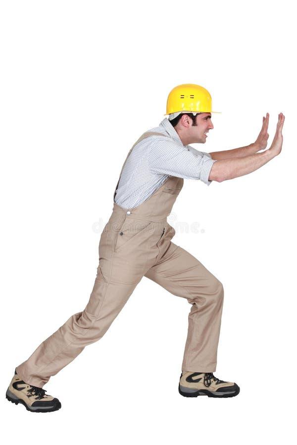 Επιστάτης που ωθεί ενάντια σε έναν τοίχο στοκ φωτογραφίες με δικαίωμα ελεύθερης χρήσης