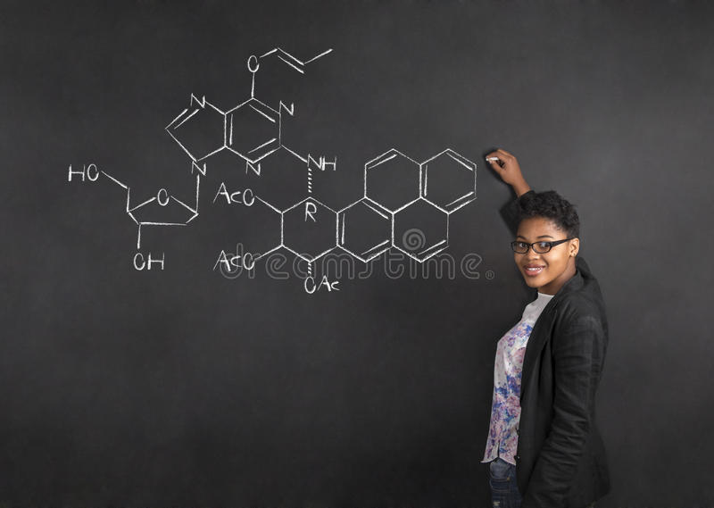 Επιστήμη γραψίματος δασκάλων γυναικών αφροαμερικάνων στο μαύρο υπόβαθρο πινάκων κιμωλίας στοκ φωτογραφία