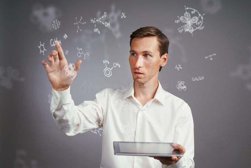 Επιστήμονας ατόμων με το PC ταμπλετών που λειτουργεί με τους χημικούς τύπους στο γκρίζο υπόβαθρο στοκ εικόνες με δικαίωμα ελεύθερης χρήσης