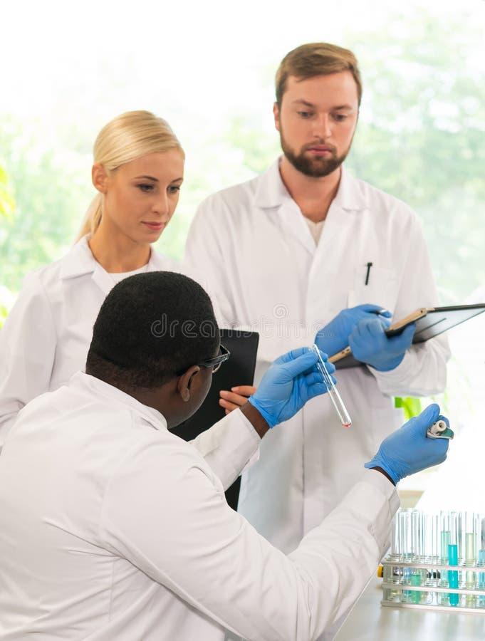 Επιστήμονας και σπουδαστές που εργάζονται στο εργαστήριο Οικότροφοι διδασκαλίας γιατρών για να κάνει το αίμα που αναλύει την έρευ στοκ εικόνες