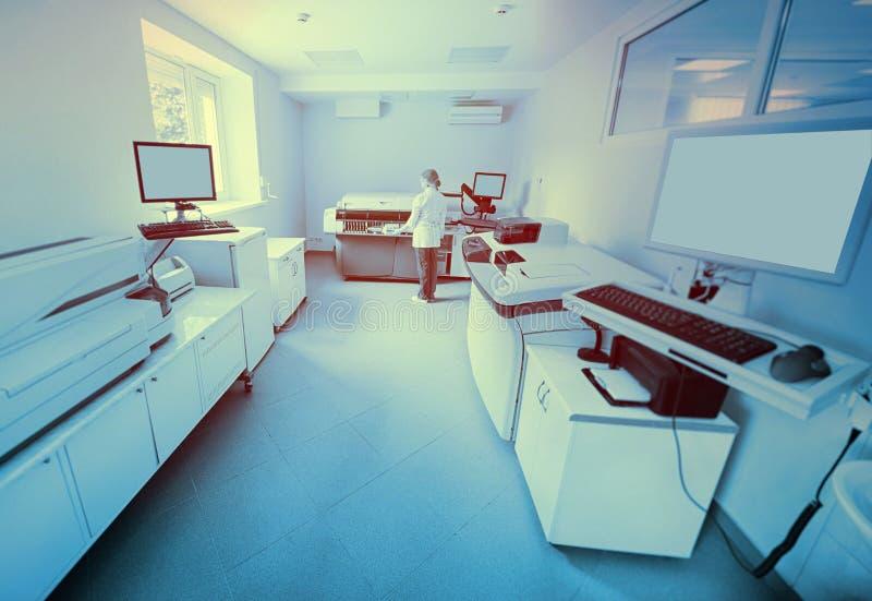 επιστήμονας κοντά στη συσκευή ανάλυσης σε ένα ιατρικό μικροβιολογικό εργαστήριο στοκ εικόνες